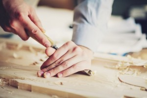 woodcarver tool cuts the wood on table